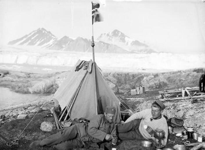 """""""Med flagget til topps i nasjonens tjeneste. Polarimperialisten Adolf Hoel (t.v.) på en av hans første Svalbard-ekspedisjoner. Her sammen med Karl Haavimb ved Blomstrandbreen i Kongsfjorden sist i juli 1907."""""""