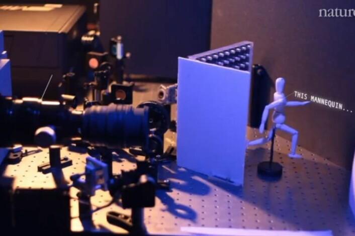Teknologien består av et kamera, en laser og en dataalgoritme. Laseren (venstre hjørne) skyter lys inn mot en vegg (ytterst til høyre), som reflekterer og sprer lyset, som dermed treffer det skjulte objektet (tremannen). Gjenstandens overflater reflekterer lyset , og noe når tilbake til kameraet (linsen til venstre). Gjenstandens 3D-struktur konstrueres utfra forskjellene i ankomsttid. (Foto: Ramesh Raskar)