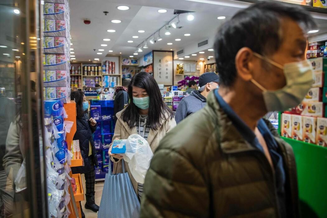 Bildet viser kunder på et apotek i Hongkong. Det rapporteres om lange køer med folk som skal kjøpe munnbind.