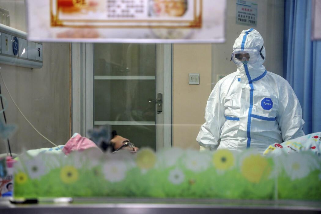 En lege ser til en pasient som er blitt isolert på et sykehus i Wuhan, byen hvor det nye koronaviruset først ble påvist. Så langt er 170 mennesker døde. Over 7 000 er smittet.