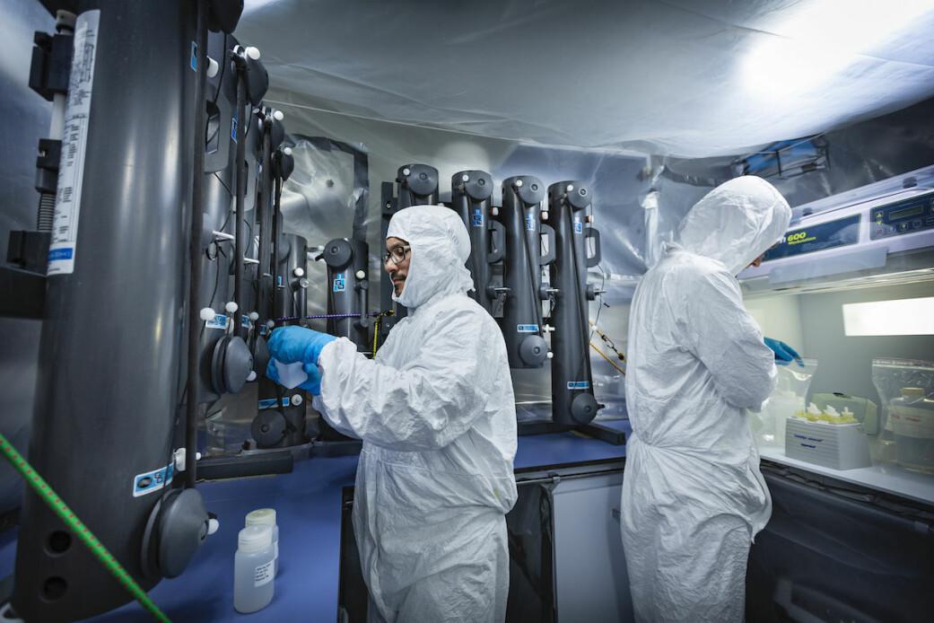 Prøver blir analysert om bord på skipet. Her er postdoktor Nicolas Sanchez og doktorgradsstipendiat Stephen Kohleri i et såkalt ultrarent rom, der en del av laboratoriet er dekket inn av plast. Draktene er for å hindre forurensning.