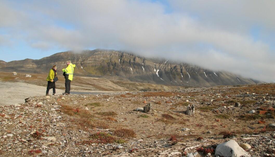 Bare tuftene står igjen av jakthytta ved Russekeila. I bakgrunnen geolog Lena Rubensdotter og arkeolog Anne Cathrine Flyen.