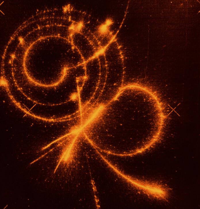 Her kan du faktisk se et avtrykk fra et myon i en partikkeldetektor. Myonet danner spiralen øverst i bildet, etter at et pion har henfalt til et myon. Tilslutt henfaller myonet til et elektron, som skyter ut fra spiralen til høyre.