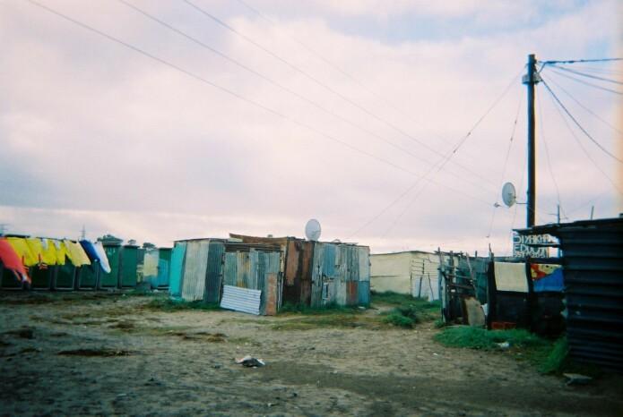 Skurene og boligene i de uformelle bosettingene er som regel satt sammen av de billigste materialene folk får ta i. Bygget rett på sandgrunnen er folk også særlig utsatt for oversvømmelse i regnsesongen. Fra stolpen til høyre i bildet ser man tydelig at folk har koblet seg ulovlig til strømnettet. Til venstre i bildet bak klærne som henger til tørk er også innbyggernes fellestoaletter. Disse er ofte stengt fordi vedlikeholdet er ikke-eksisterende. På natten bruker innbyggerne en bøtte som de har innendørs fordi det er for risikabelt og gå ut på natten. Overgrep og kidnapping av barn er en reell frykt.