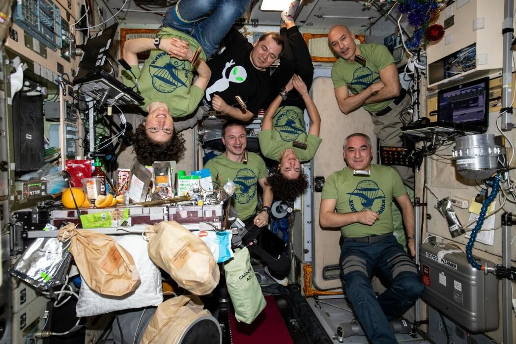 Vil du også spise mat i utfordrende omgivelser på romstasjonen? Dette er mannskapet på ISS nyttårsaften 2019, før de skal innta et festmåltid.