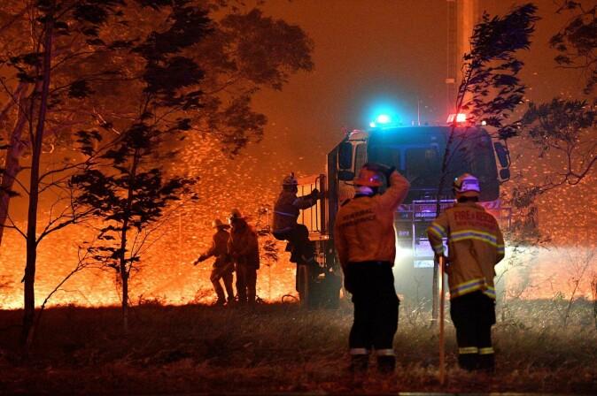 Brannmenn står foran flammehavet 31. desember 2019 i Nowra i Australia.