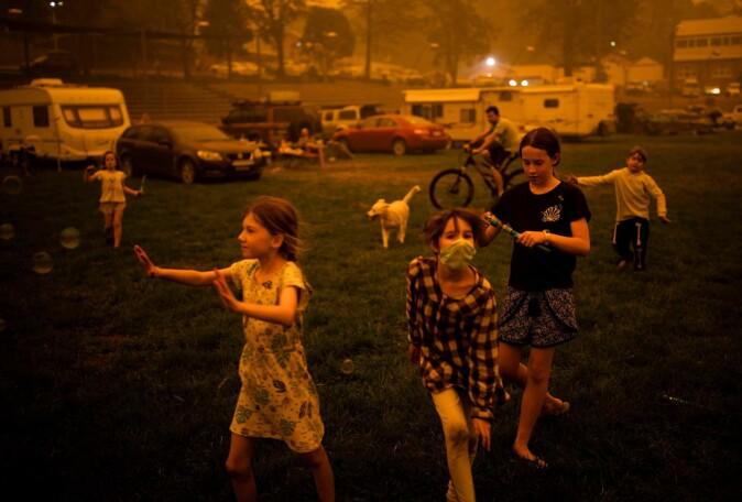 Barn leker på en lekeplass, der luften er farget gul av røyken fra skogbrannene.