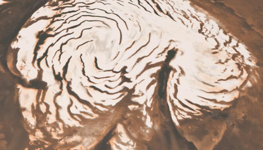 Nordpolkalotten på Mars, som er rik på vann-is. Den er ca. 1000 kilometer i diameter. Kløften Chasma Boreale skjærer inn i den på høyre side. Mørke, spiralformede bånd er mindre kløfter. (Foto: NASA/Caltech/JPL/E. DeJong/J. Craig/M. Stetson)