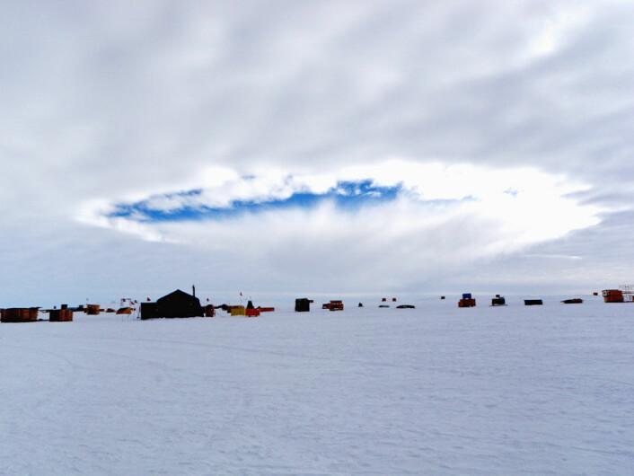 Hull i skydekket over en forskningsbase på Antarktis, forårsaket av et fly. Bildet er tatt ved West Antarctic Ice Sheet Divide Camp i desember 2009. Hullet i skydekket, som antagelig skyldes et LC 130 transportfly, dukket først opp på horisonten og beveget seg deretter mot kameraet. (Foto: Erik Zrubek og Michael Carmody/Science/AAAS)