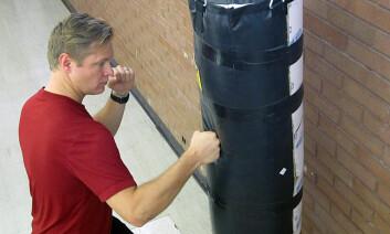 Medisinstudent Michael H. Morgan slår på en fylt sekk. Sammen med professor David Carrier har han gjennomført forsøk for å se på utviklingen av menneskets hender. (Foto: Lee J. Siegel, University of Utah)