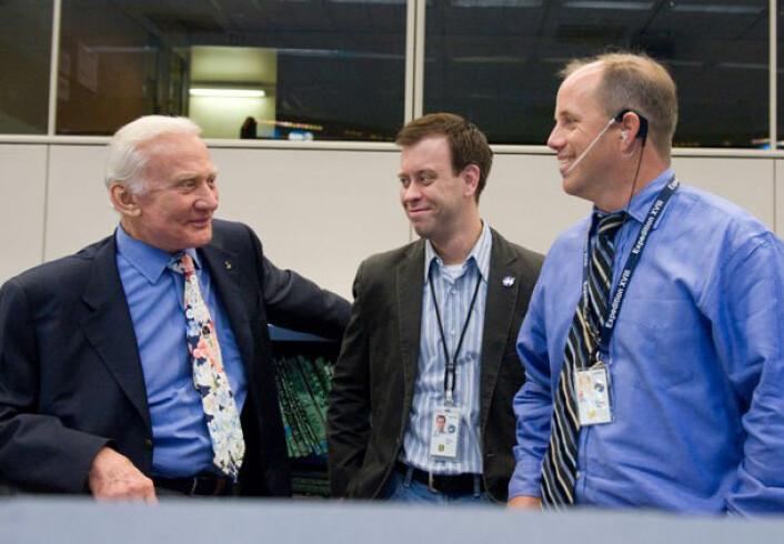 Edwin Aldrin (t.v.) sammen med NASA-talsmann Josh Byerly og Flight Director Ron Spencer i kontrollrommet for Den internasjonale romstasjonen, juli 2009. (Foto: NASA/Harnett)