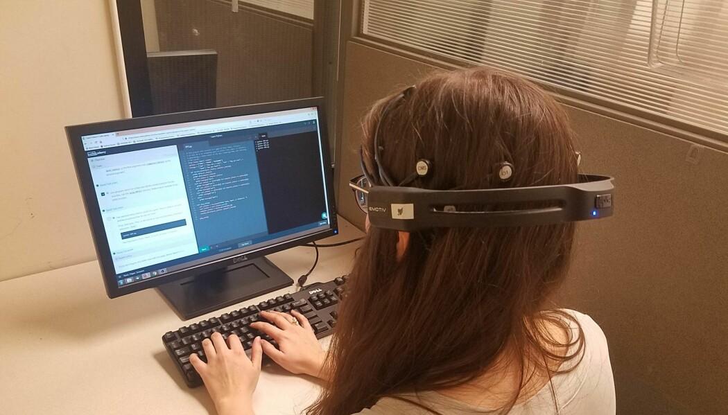 En av forskerne, Malayka Mottarella, viser koding mens et apparat måler hjerneaktiviteten hennes.