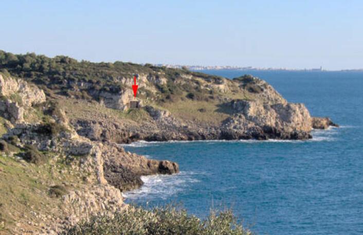 Grotta del Cavallo ligger ved en bukt på kysten av Puglia i Sør-Italia. Åpningen er merket med en rød pil. Hulen ligger i naturreservatet Regional National Park of Portoselvaggio. Bukta heter Uluzzo, samme navn har arkeologene brukt på funn av denne typen fra det sentral og sørlige Italia. (Foto: Annamaria Ronchitelli)