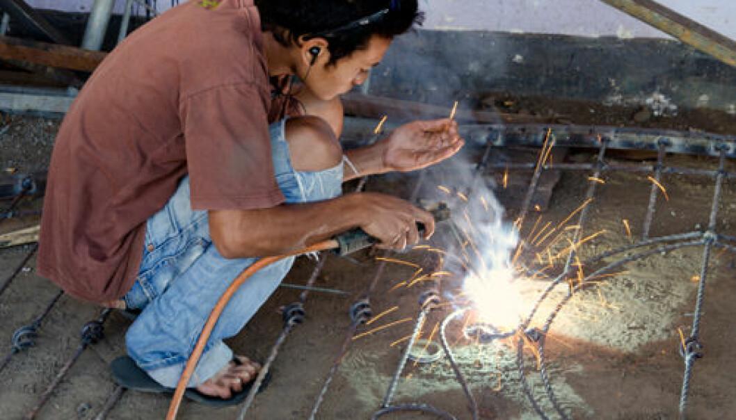 En ung indonesisk mann sveiser et stålgjerde uten beskyttelse for øynene eller annet verneutstyr. iStockphoto