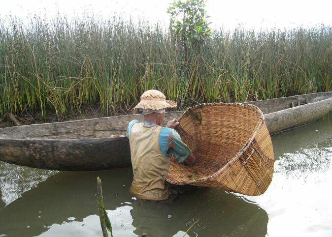 Denne fiskeren leter etter reker i en elv i Madagaskar.