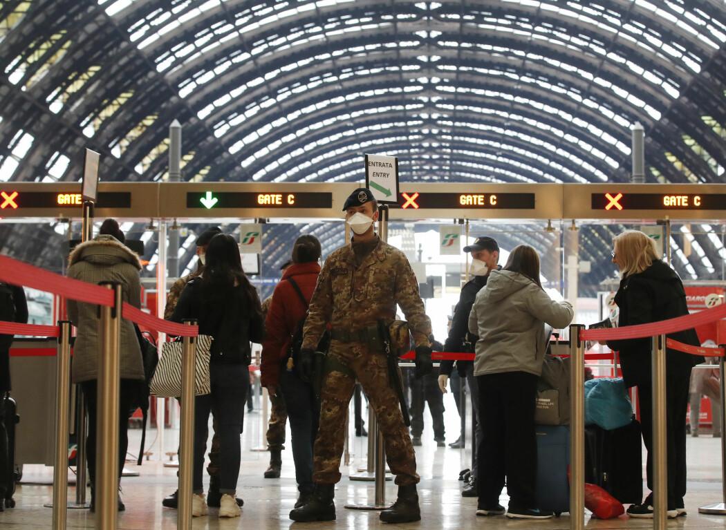 Politifolk og soldater med ansiktsmasker sjekker passasjerer på den største jernbanestasjonen i Milano mandag.
