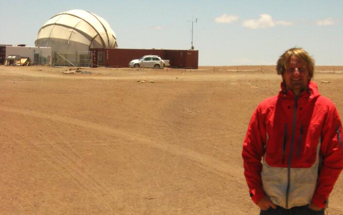 Kosmolog Jostein Riiser Kristiansen ved mikrobølgeteleskopet QUIET, 5000 m.o.h i Atacame-ørkenen i Chile. QUIET studerer mikrobølger som stammer fra like etter Big Bang, da universet var bare 380 000 år gammelt. Det er altså bølger som har reist i nesten 14 milliarder år før de blir fanget opp av teleskopet. (Foto: Privat)