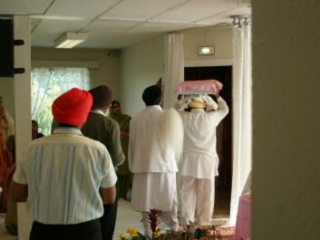 """""""Den hellige boken Guru Granth Sahib, som behandles som en levende guru, bæres til sitt sengeleie."""""""