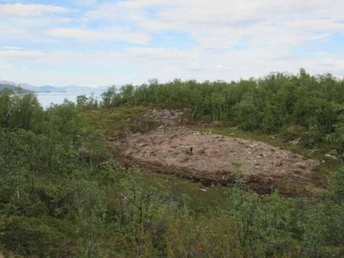 Litt av utgravingsområdet bak Larshaugen i Melsvik. I bakgrunnen sees Altafjorden og Isnestoften i det fjerne. Den avdekkede delen av steinbruddet i berget sees til venstre for utgravingsområdet. (Foto: Tromsø Museum - Universitetsmuseet)
