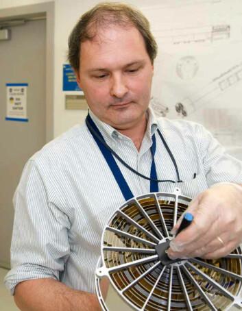 Sjefsforsker Keith Gendreau med et røntgenspeil som ligner ett av de 56 på NICER/SEXTANT. De konsentriske ringene fungerer som røntgenspeil, med svært slak vinkel mot retningen fra strålene. (Foto: Bill Hrybyk)