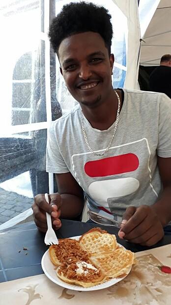 """Vafler er ikke like utbredt i alle verdenshjørner. Amaniel, en vaffelentusiast fra Eritrea, hadde ikke smakt vafler før han kom til Norge. Det tok imidlertid ikke lang tid før han gikk til innkjøp av eget vaffeljern. """"Vafler er kjempegodt"""", sier han - og han har ingen kulturelle begrensninger knyttet til vaffelpålegg. """"Sprøstekt løk er jo godt på pølse, så hvorfor ikke forsøke rømme og løk på vaffel også?"""""""
