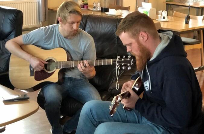 Lege Thomas Dretvik (t.v.) og mekaniker Arthur Snekvik jammer gjerne på gitarene når de slapper av innendørs på Troll.