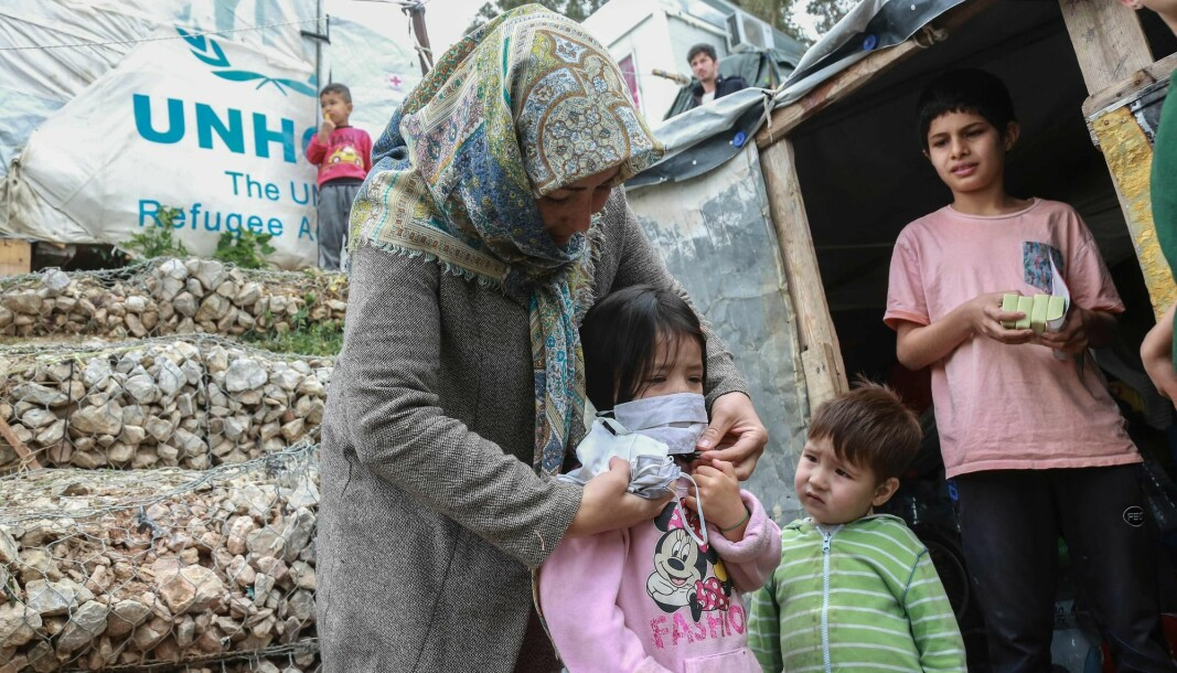 A woman helps a child with a mask after members of NGO