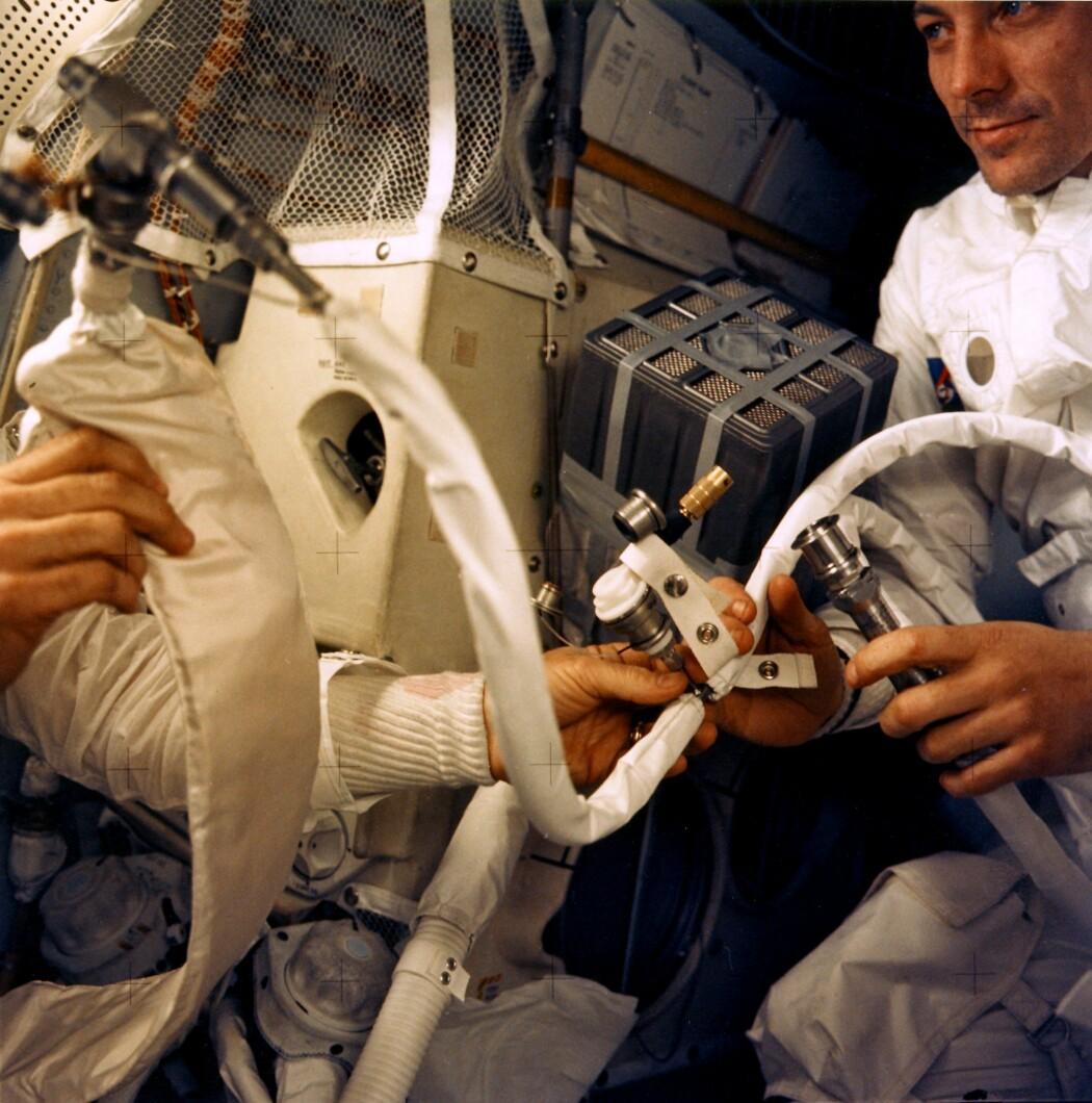 Astronautene ombord på Apollo 13 under ferden. Til høyre ser du John Swigert, og i midten av bildet er den berømte, improviserte filterboksen som skulle rense lufta i modulen for CO2.