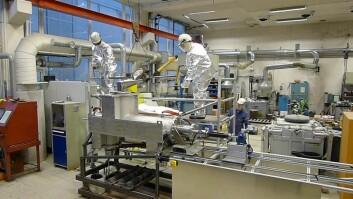 Arne Nordmark og Kurt Sandaunet i jobb med maskinen i sine varmereflekterende, sølvfargede dresser. (Foto: Sintef)