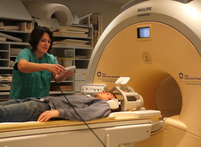 Radiograf Grethe Løvland hjelper forskning.nos journalist Per Byhring på plass i fMRI-maskinen i Intervensjonssenteret på Oslo Universitetssykehus, Rikshospitalet. (Foto: Arnfinn Christensen, forskning.no)
