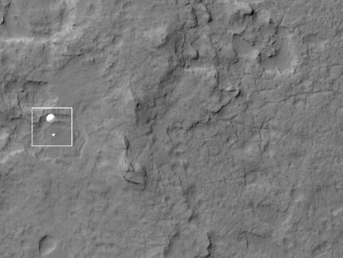 Kapselen med rombilen Curiosity henger fint under den spesialkonstruerte fallskjermen. Bildet viser at skjermen er fullt utslått og fungerer akkurat som den skal. (Foto: NASA/JPL-Caltech/University of Arizona)