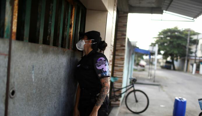 En politikvinne sjekker om det går bra med en kvinne som har vært utsatt for vold i hjemmet i Brazil nå som koronaviruset har ført til at folk er mer isolerte i hjemmene sine.
