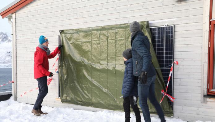 Direktør i NVE, Kjetil Lund og en elev fra Husøy skole avdekker solcellepaneler som skal forsyne skolen med energi. Avdukingen markerte åpningen av prosjektet Smart Senja.