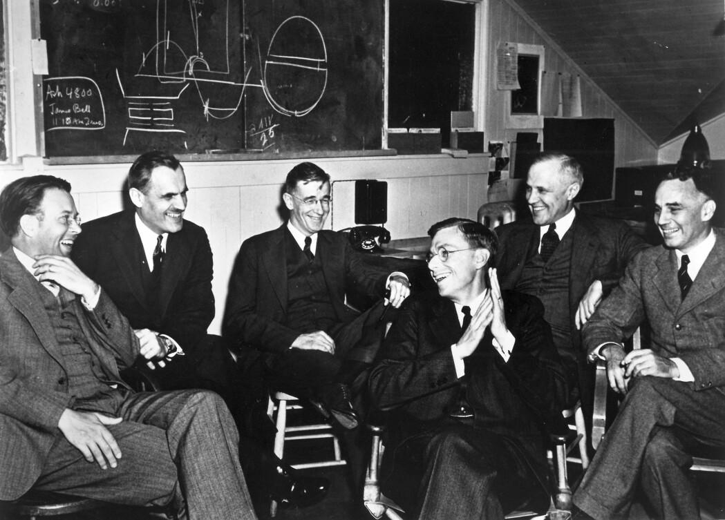 Fysikere ved University of California, Berkeley, med nobelprisvinner Ernest Lawrence (lengst til venstre) i spissen under et møte i 1940. Denne forskergruppa hadde ansvaret for en bit av det som skulle bli det teoretiske grunnlaget for atombomben.