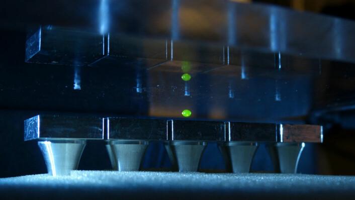 Mellom to plater - den nederste sendte lydbølger oppover og den øverste reflekterte dem ned igjen - klarte forskerne å holde og smelte sammen dråper på en kontrollert måte. Foto: Dimos Poulikakos.