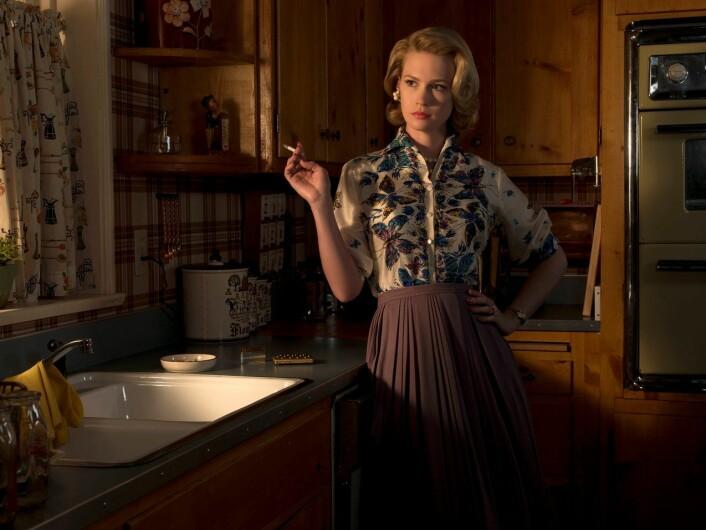 Betty Draper iscenesetter seg selv på kjøkkenet i TV-serien «Mad Men». En perfekt fasade med realistisk 60-tallskoloritt skjuler et ulykkelig liv. – Hun er en husmor fanget på kjøkkenet som ser lengtende ut av vinduet på friheten, sier TV-viter Gry Rustad. (Foto: Album)