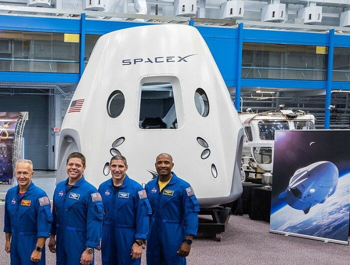 De fire første astronautene som skal fly med Crew Dragon, foran en modell av romskipet.