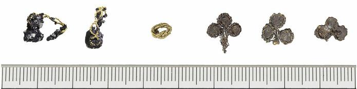 De seks edelmetallgjenstandene funnet i grava. Helt til venstre er de to gullringene med hver sin perle, så den lille gullperla og de tre sølvplatene med forgylte tråder til høyre.