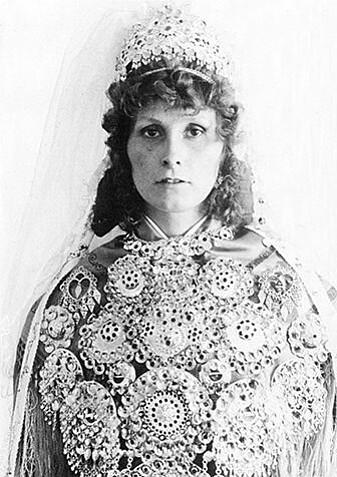 Figur 1: Kvinne i samisk kofte med brudesøljer og brudekrone. I eldre nordiske og samiske drakttradisjoner viste tilbehør som søljer, belter og hodeplagg tydelig om du var gift eller ugift, og egne smykkeoppsett og kroner ble brukt i forbindelse med bryllup.