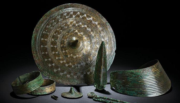 Figur 2: Smykkene som fulgte Regekvinnen i graven, datert til 1500–1300 f. Kr. I midten den store belteplaten og en mindre tutulus foran den. På venstre side to armringer og røret som har vært festet på et snoreskjørt. Til høyre for smykkeplatene en dolk, en fibula og en stor halskrave, alt av bronse.