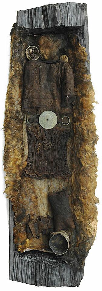 Figur 3: Egtvedpikens grav med den svært godt bevarte ulldrakten. Begravelsen er tidfestet til år 1370 f. Kr. Belteplaten er festet i beltet. På hver side av denne er det armringer. Ved hodet og føttene er det beholdere av bark. I den ene lå det en syl og et hårnett. Kammen av horn som er plassert ved hodet, har opprinnelig sittet i beltet. På beina har hun hatt såkalte fotlapper av ull.