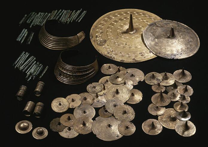 Figur 4: Offerfunnet fra Vognserup Enge, datert til 1500–1300 f. Kr. Smykkene kan deles inn i to sett. Til venstre en mengde rør til et snoreskjørt samt to store halskraver og fire små spiralringer. Også halskravene har spiralornamentikk. Til høyre to store belteplater og en mengde tutuli.