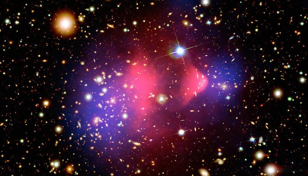 Det røde området i midten viser røntgenstråling fra to kolliderende galaksehoper, fotografert med romteleskopet Chandra. Vanlig materie ble bremset opp i kollisjonen (rødt), mens den mørke materien fortsatte tvers gjennom, upåvirket (blått). Den mørke materien er tegnet inn i fotografiet, da den ikke kunne påvises direkte, bare måles ut fra hvordan tyngdekreftene deres avbøyde lysstråler fra galaksene. NASA/CXC/M. Weiss