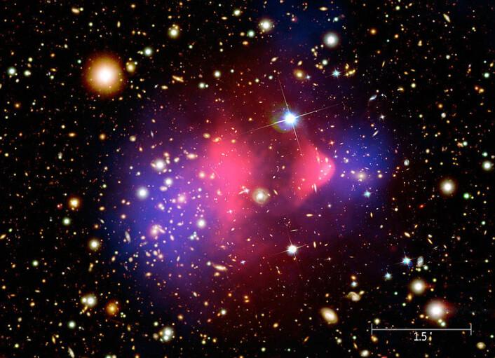 Det røde området i midten viser røntgenstråling fra to kolliderende galaksehoper, fotografert med romteleskopet Chandra. Vanlig materie ble bremset opp i kollisjonen (rødt), mens den mørke materien fortsatte tvers gjennom, upåvirket (blått). Den mørke materien er tegnet inn i fotografiet, da den ikke kunne påvises direkte, bare måles ut fra hvordan tyngdekreftene deres avbøyde lysstråler fra galaksene. (Foto: NASA/CXC/M. Weiss)