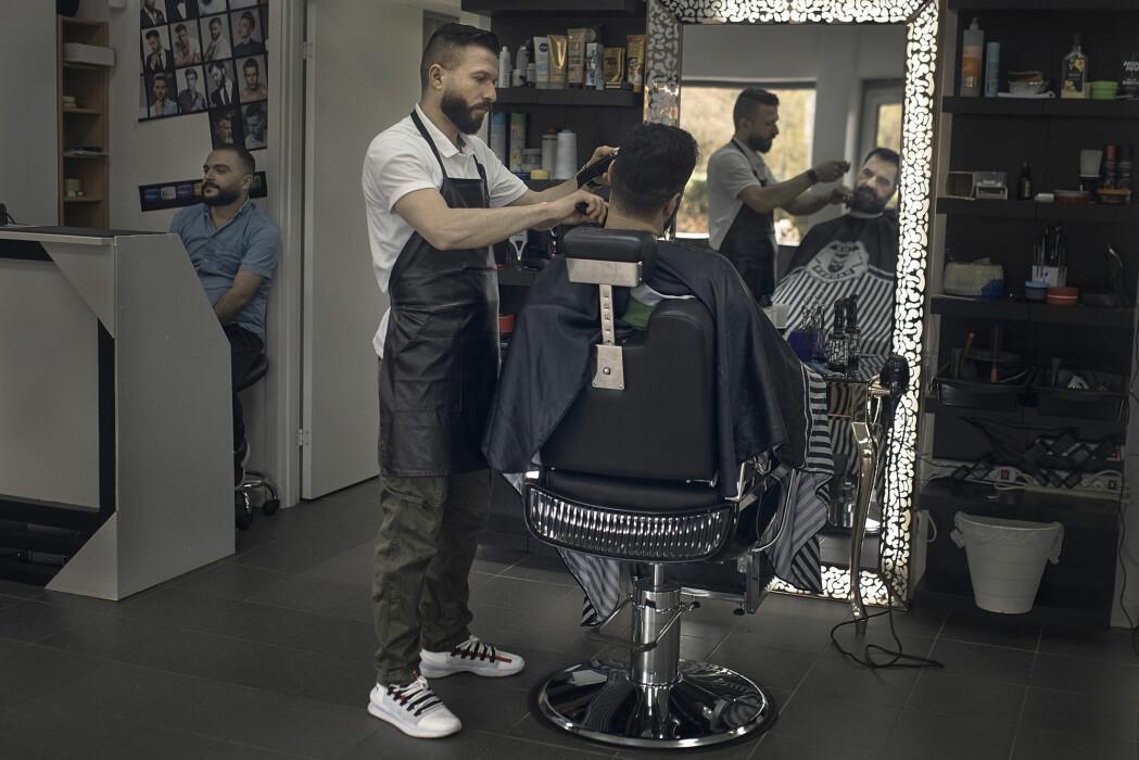Frisøren Hasan Derek klipper en kunde i en salong i Akalla i bydelen Rinkeby-Kista i Stockholm. I pandemien har Sverige valgt en linje med langt mindre restriksjoner og nedstengning enn andre land.