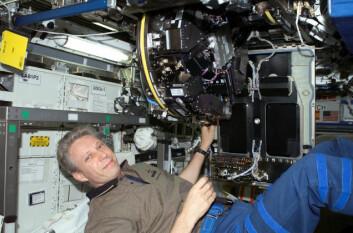 Astronaut Thomas Reiter monterer et av vekstkamrene for planteforsøk ombord på romstasjonen. (Foto: ESA/NASA)