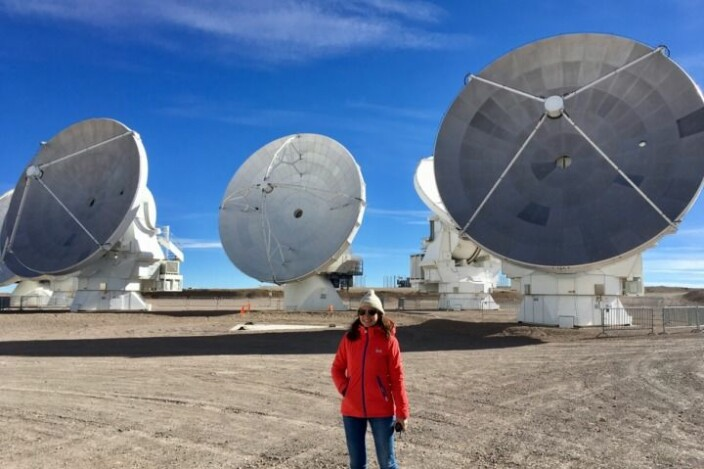 Claudia Cicone and the antennas of the Atacama Large Millimeter/sub-millimeter Array (ALMA). Their diameter is 12 metre, while AtLAST is designed to be four times bigger.