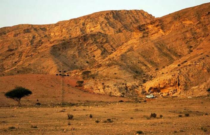 I dette ørkenlandskapet i De forente arabiske emirater fant arkeologer spor av det som kan være de første menneskenes vei ut av Afrika. Boplassen ved Jebel Faya er rett bak bilen på bildet. (Foto: Science/AAAS)