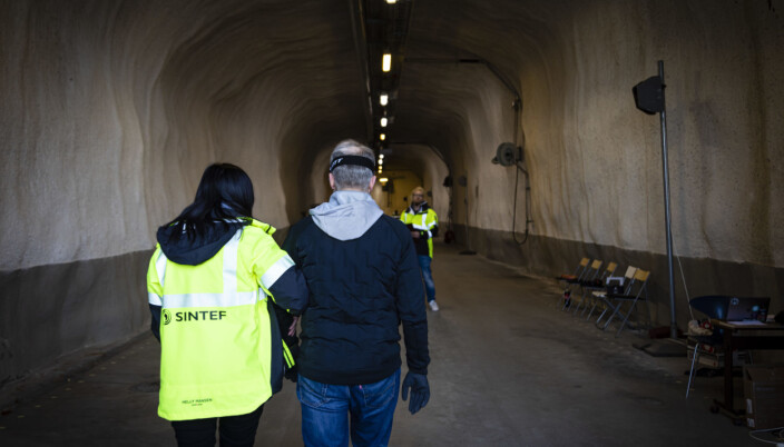 Here we see one of the research subjects being led through the tunnel, wearing glasses that make it impossible for him to see where he is going. The sound system developed by the researchers simulates the noises made by the tunnel fans during a fire, while at the same time testing the new auditory guidance system.