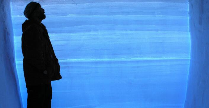 En forsker står ved siden av en iskjerne fra Vest-Antarktis. Hver av de horisontale strekene i iskjernen representere ett års snøfall. I alt dekker iskjernen 68 000 år klimahistorie. (Foto: Kendrick Taylor/Desert Research Institute)
